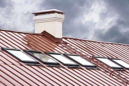 nieuwe rode metalen dak met dakramen en schoorsteen