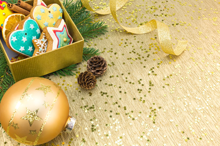 gingerbread cookies: christmas gift box with gingerbread cookies and decoration on golden festive background