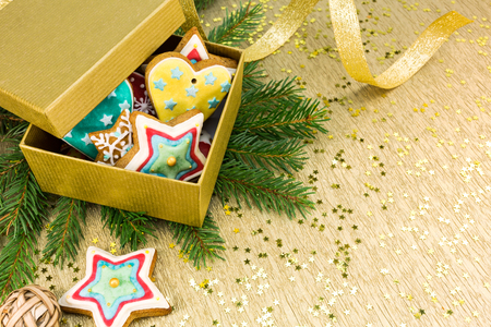 gingerbread cookies: gift box with colorful christmas gingerbread cookies on gold wrapping paper background