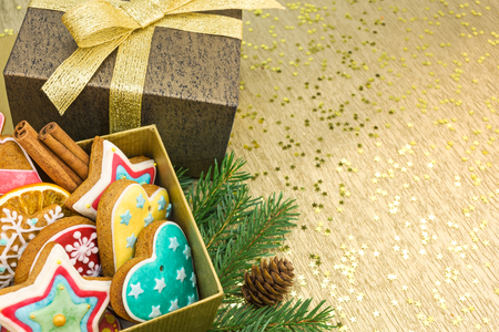 gingerbread cookies: christmas decorations with gift boxes and gingerbread cookies on gold background