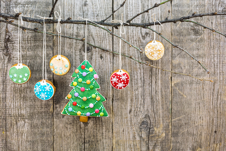 group of christmas baubles: gingerbread christmas tree with cookies hanging over aged wooden background