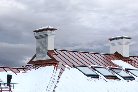 skylights: red metal roof covered by snow with chimneys and skylights