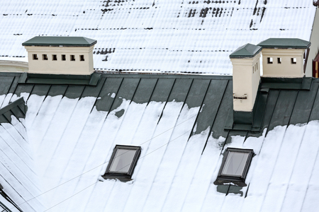skylights: brown metal roof covered by snow with skylights and chimneys