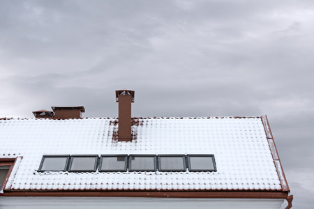 skylights: snow covered roof with skylights and chimney
