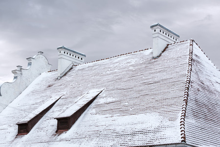 dormer: tiled roof of old house with dormer windows and chimneys under snow Stock Photo