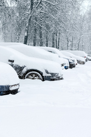 cars covered with snow on a parking lot during snowfall