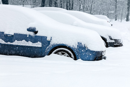 wintery day: parked cars covered with snow in winter blizzard