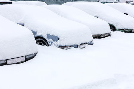 a blizzard: parked cars covered with snow in winter blizzard