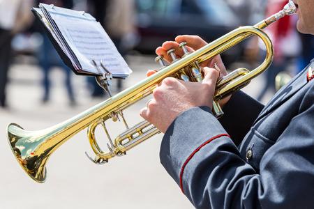 trompeta: músico militar tocando la trompeta de oro en banda de música del ejército