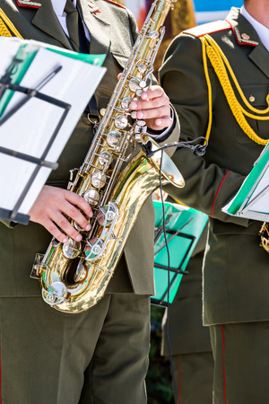 saxophones: military musician playing gold saxophones on street concert