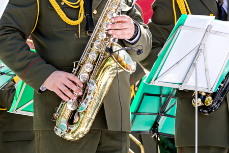 saxophones: military musicians playing gold saxophones on street concert Stock Photo