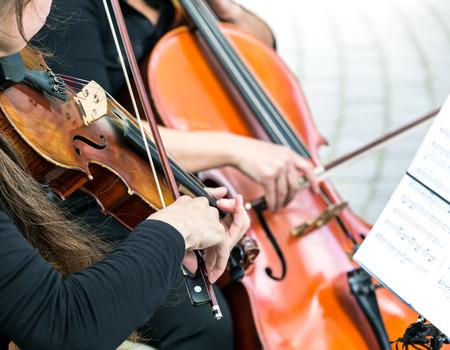 orquesta clasica: niñas de las manos tocando el violín en la orquesta de la calle