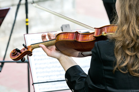 fiddlestick: violin in the hands of a musician in street orchestra