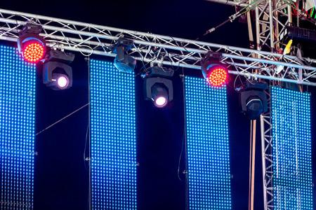 illuminate: bright multicolored spotlights illuminate outdoor concert stage