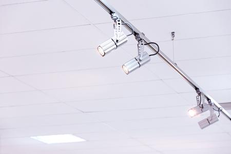 halogen lighting: row of bright halogen spotlights on exhibition ceiling