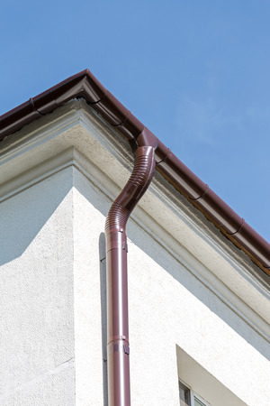 roofing system: new rain gutter on a home against blue sky