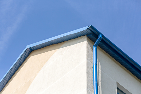 roofing system: rain gutter on house with blue sky in the background