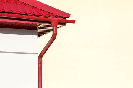 roofing system: corner of a house with gutter and red tiled roof