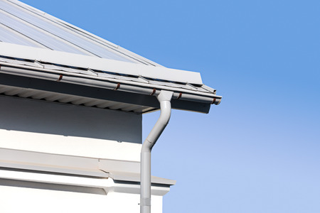 roofing system: new gray metal rain gutter on house rooftop against blue sky