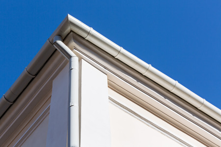 overhang: new rain gutter on a home against blue sky