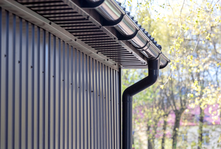 gutter: brown siding wall with plastic rain gutter and drainpipe
