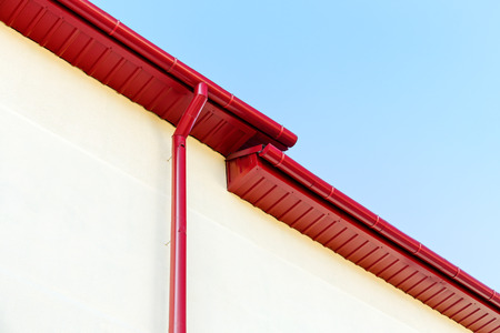 roofing system: roof gutter with drainpipe on house plaster wall Stock Photo