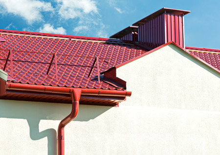 roofing system: house with new red tiled roof and gutter under blue sky