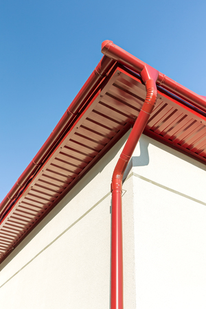 roofing system: newly installed red rain gutter and drainpipe