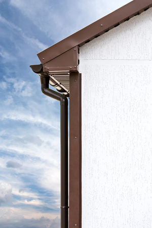 roofing system: brown PVC downspout on wall against sky background