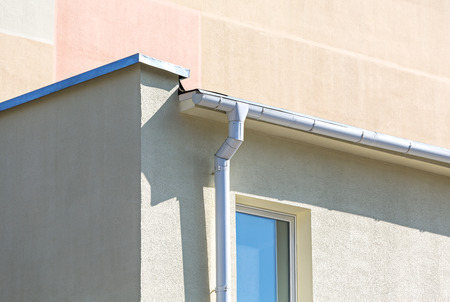 roofing system: white metallic gutter and drainpipe on plaster wall of building