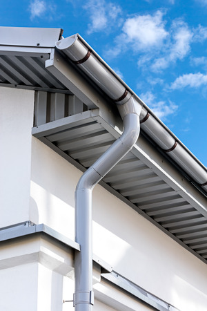 newly installed gray rain gutter on house rooftop