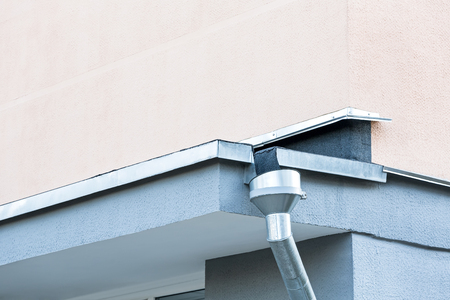 roofing system: corner of building with new galvanized rain gutter Stock Photo