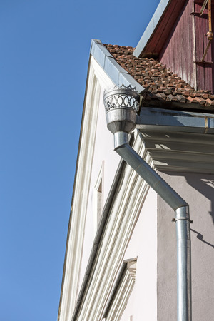 roofing system: decorative rain gutter and downspout on wall of old house