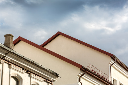 gables of old houses with new metal tile roof and gutter