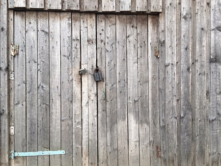 Weathered old wooden barn door with padlock background