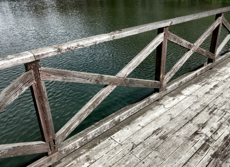 bannister: wooden foot bridge on lake in the park