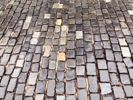 rough road: old rough granite wet cobblestone road after rain Stock Photo