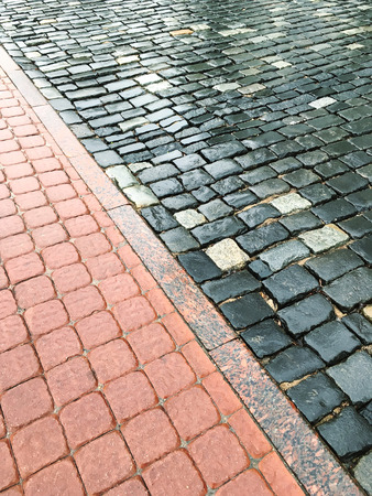 cobblestone road: wet old granite cobblestone road with colored cement brick sidewalk Stock Photo