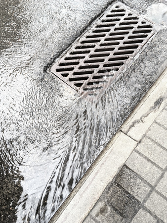 grate: rain water flows down through sewer grate on street Stock Photo