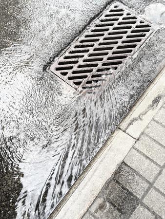 rain water flows down through sewer grate on street
