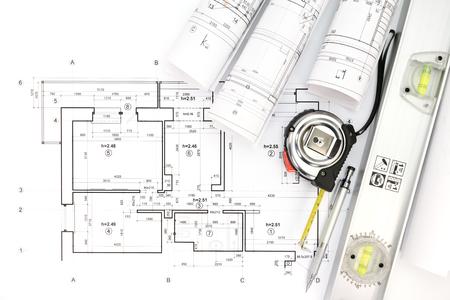 rollen van architectonische blauwdrukken en technische tekeningen met potlood, meetlint en waterpas