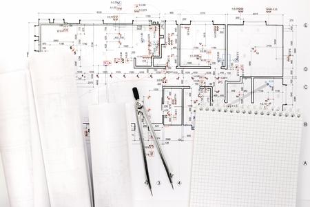 compas de dibujo: planos arquitectónicos y rollos de plano con dibujo brújula y el bloc de notas