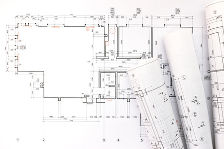 architects workspace with rolled construction plans and blueprints