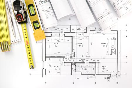 rollen van architecturale blauwdrukken en technische tekeningen met potlood, meetlint en waterpas Stockfoto