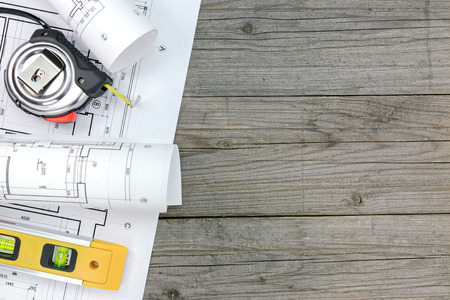 spirit level: architectural blueprints with spirit level and tape measure on gray wooden boards