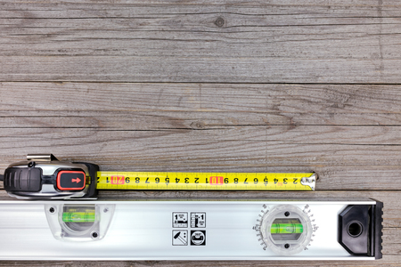 spirit level: spirit level with tape measure on gray wooden background
