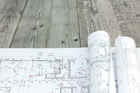 floor plan drawings with rolled architectural blueprints on wooden background