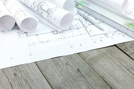 spirit level: rolls of blueprints with floor plan and spirit level on grey wooden desk