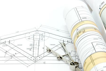 compas de dibujo: architectural blueprint rolls with plan and drawing compass Foto de archivo