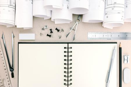 compas de dibujo: espacio de trabajo de arquitecto con planos, el bloc de notas, el compás de dibujo, lápiz, regla en el escritorio Foto de archivo